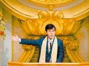 Master Okawa in front of wheel of Dharma.
